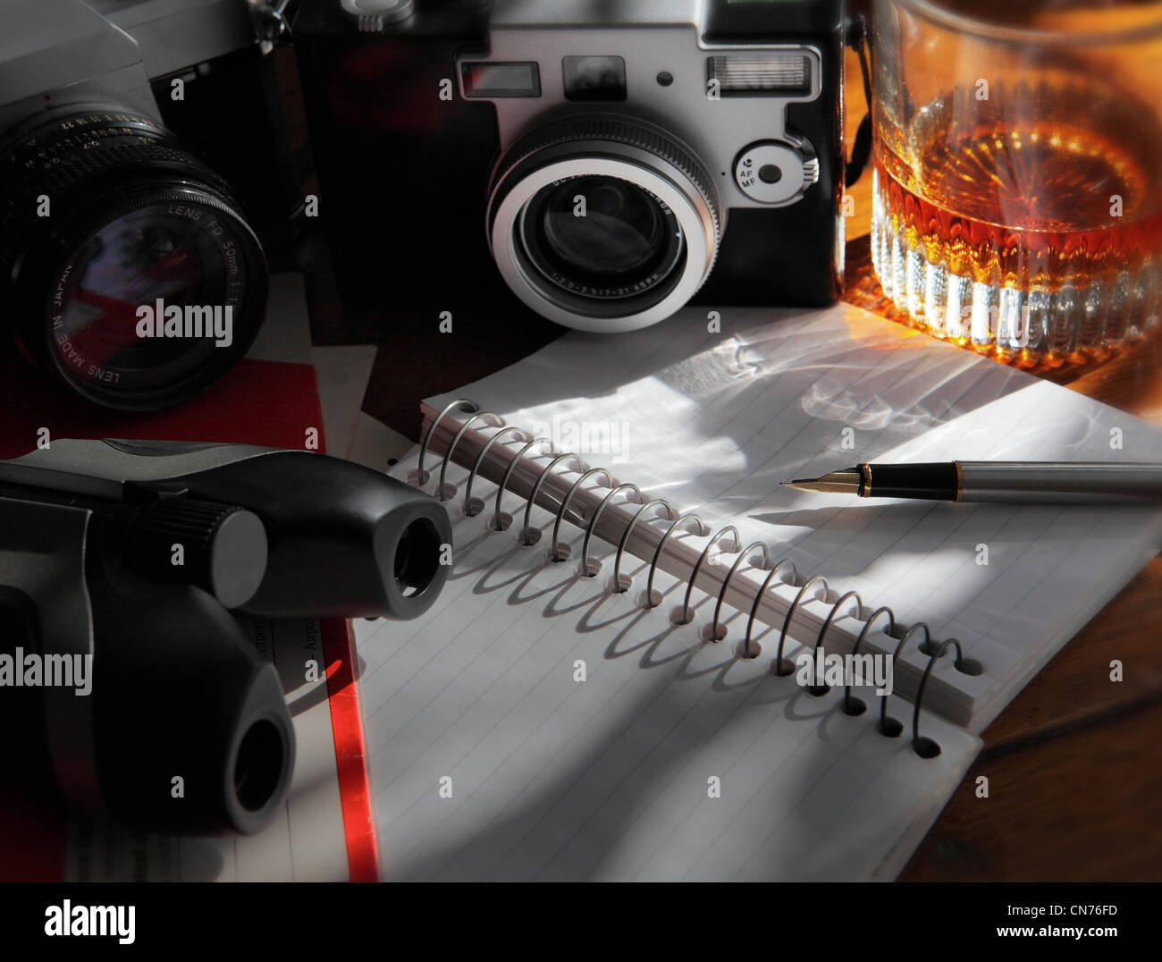 cameras, binoculars,  a liquor glass,  and an open journal and pen resting on a wooden table - Stock Image