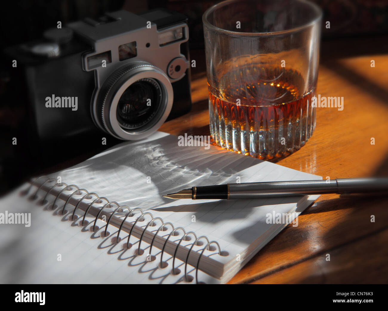 a pen resting on an open journal page, a camera and a liquor glass on a wooden table - Stock Image