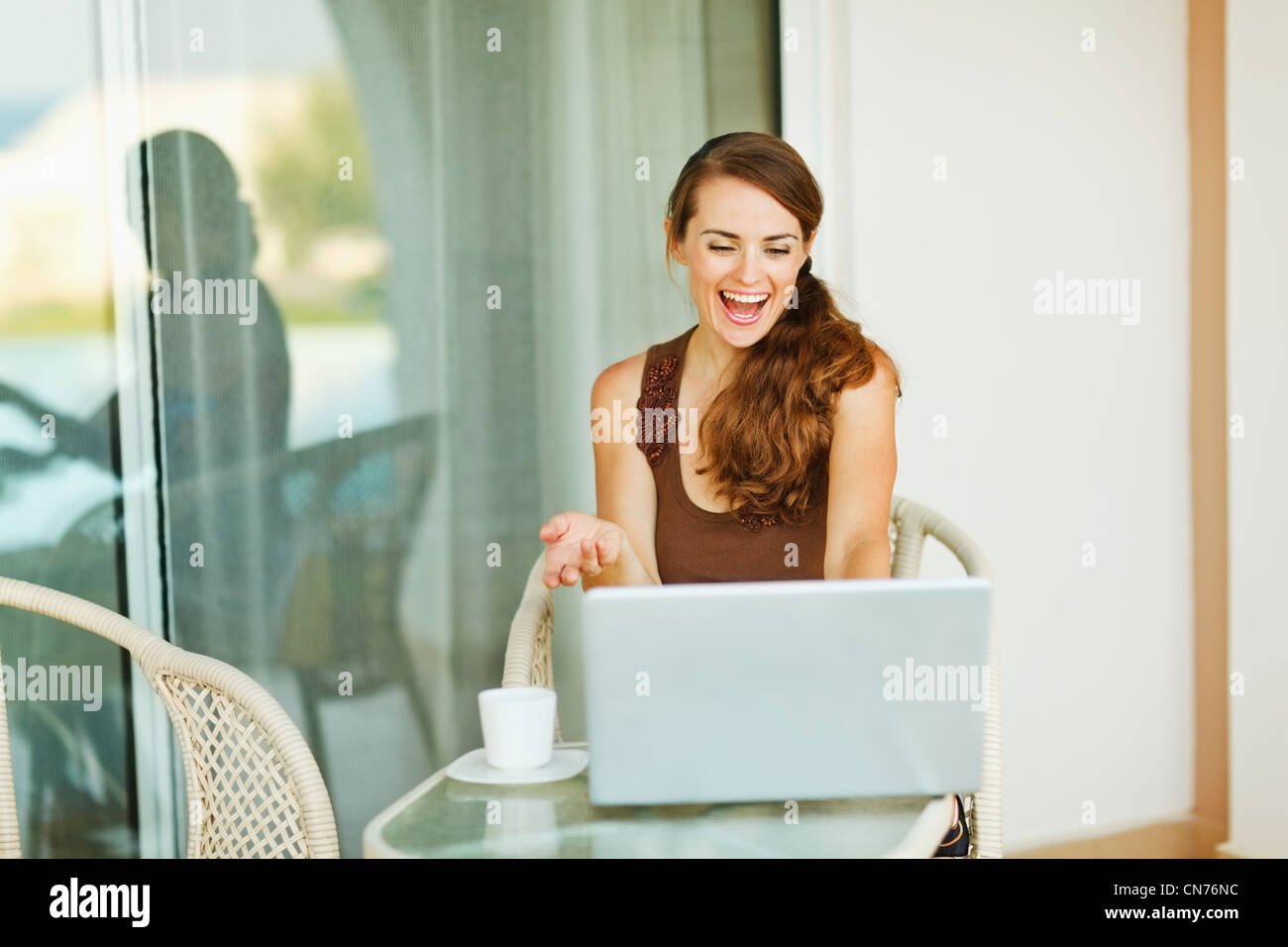 Excited young woman working on laptop on terrace with cup of coffee Stock Photo