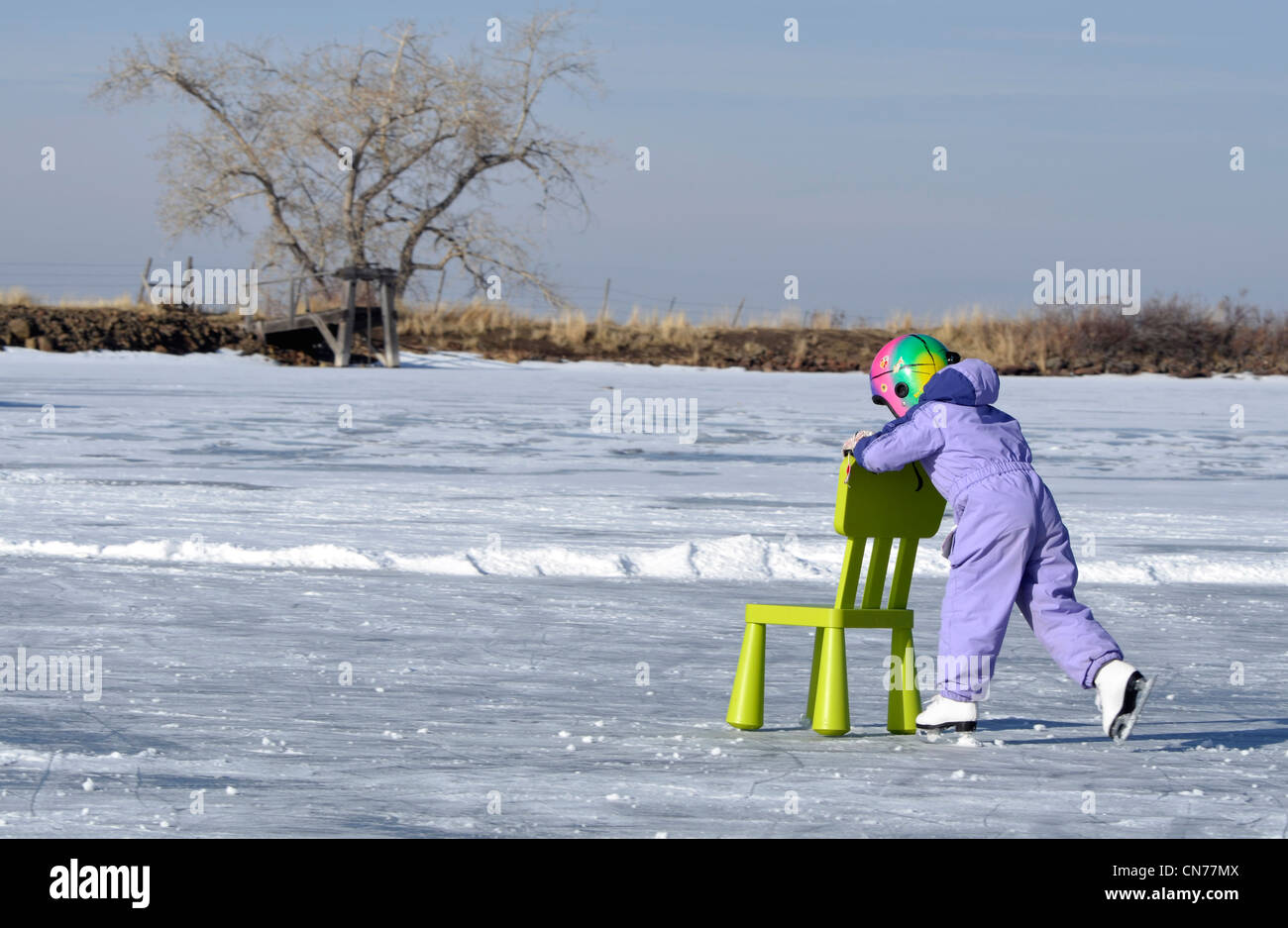 Girl using chair for leverage as she learns to ice skate on a frozen lake. - Stock Image