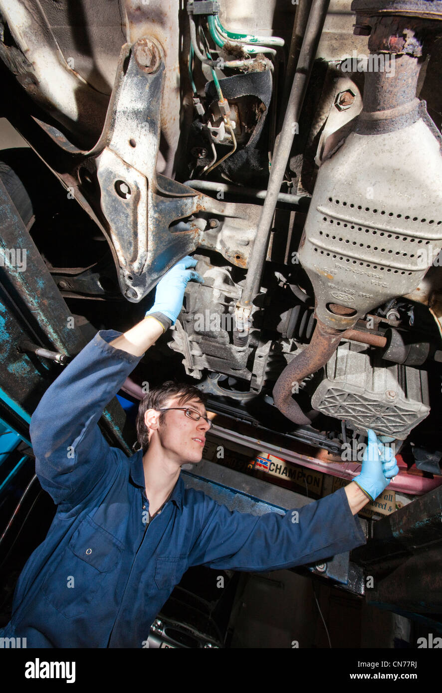 A young motor vehicle mechanic in his early twenties working underneath a car. - Stock Image