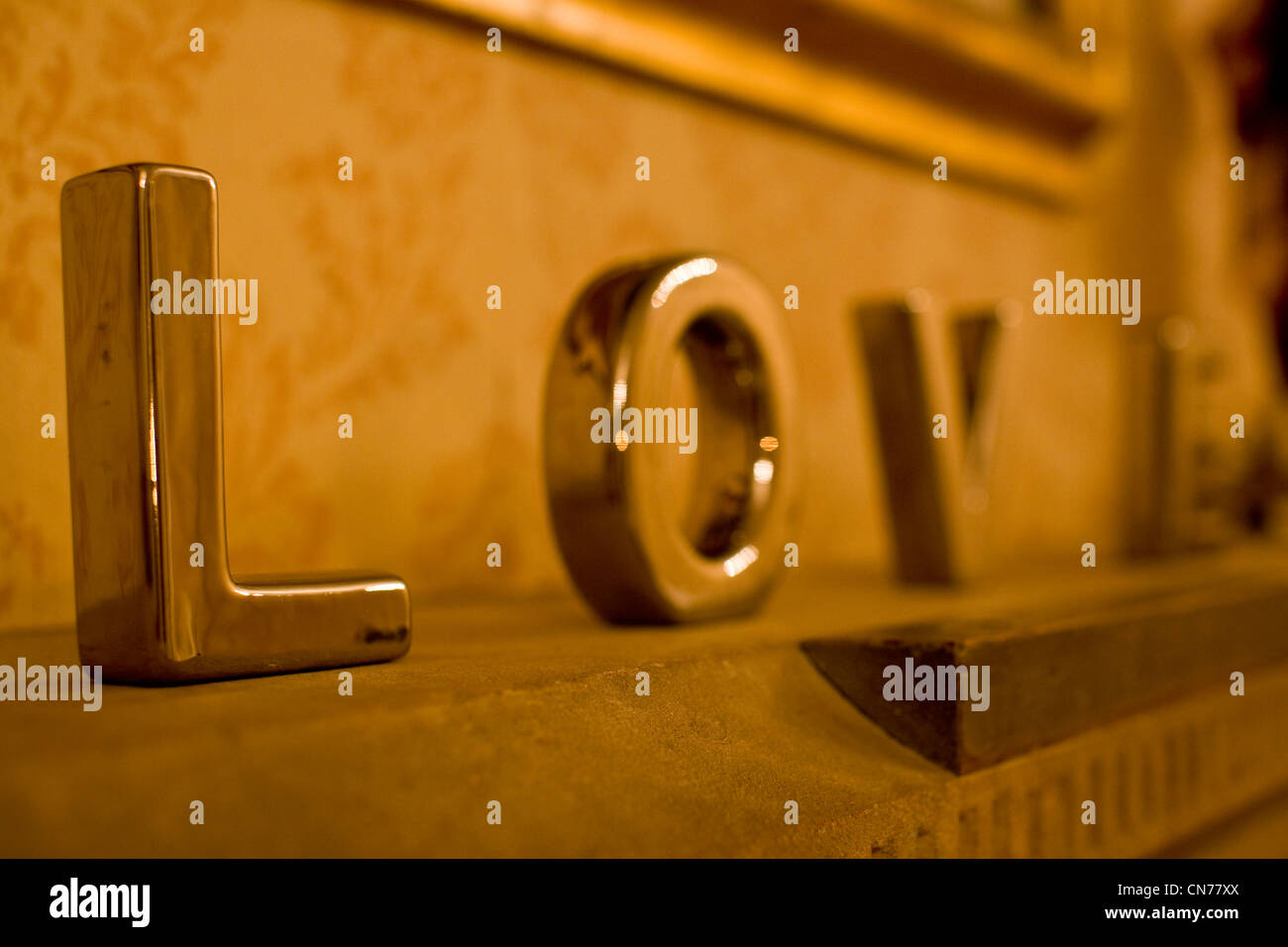 Silver metal letters spelling the word Love on a mantle piece at a wedding - Stock Image