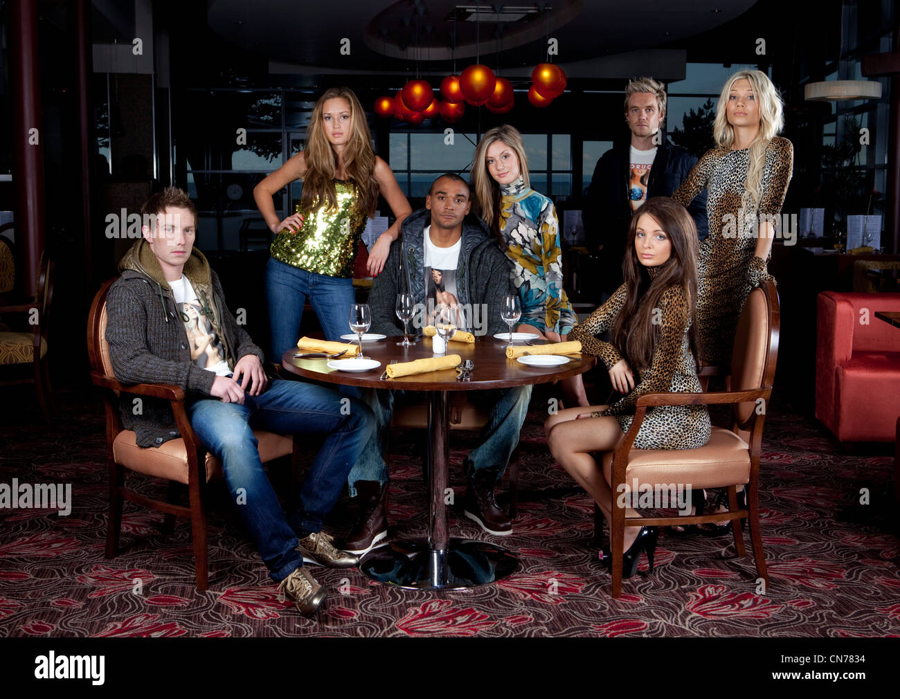 A group of young friends in their early twenties / late teens at a restaurant on a night out. - Stock Image