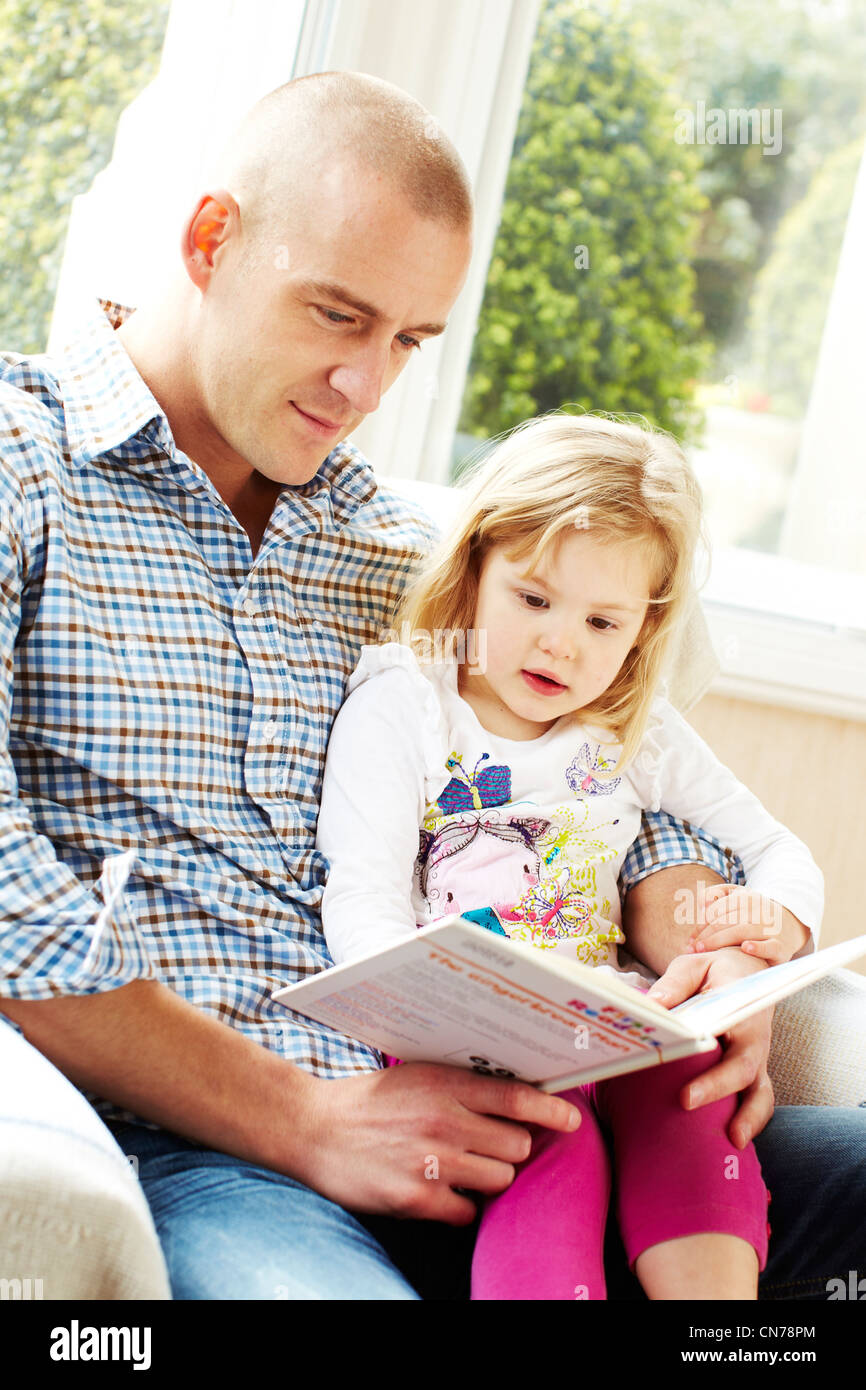 Father and daughter reading together - Stock Image
