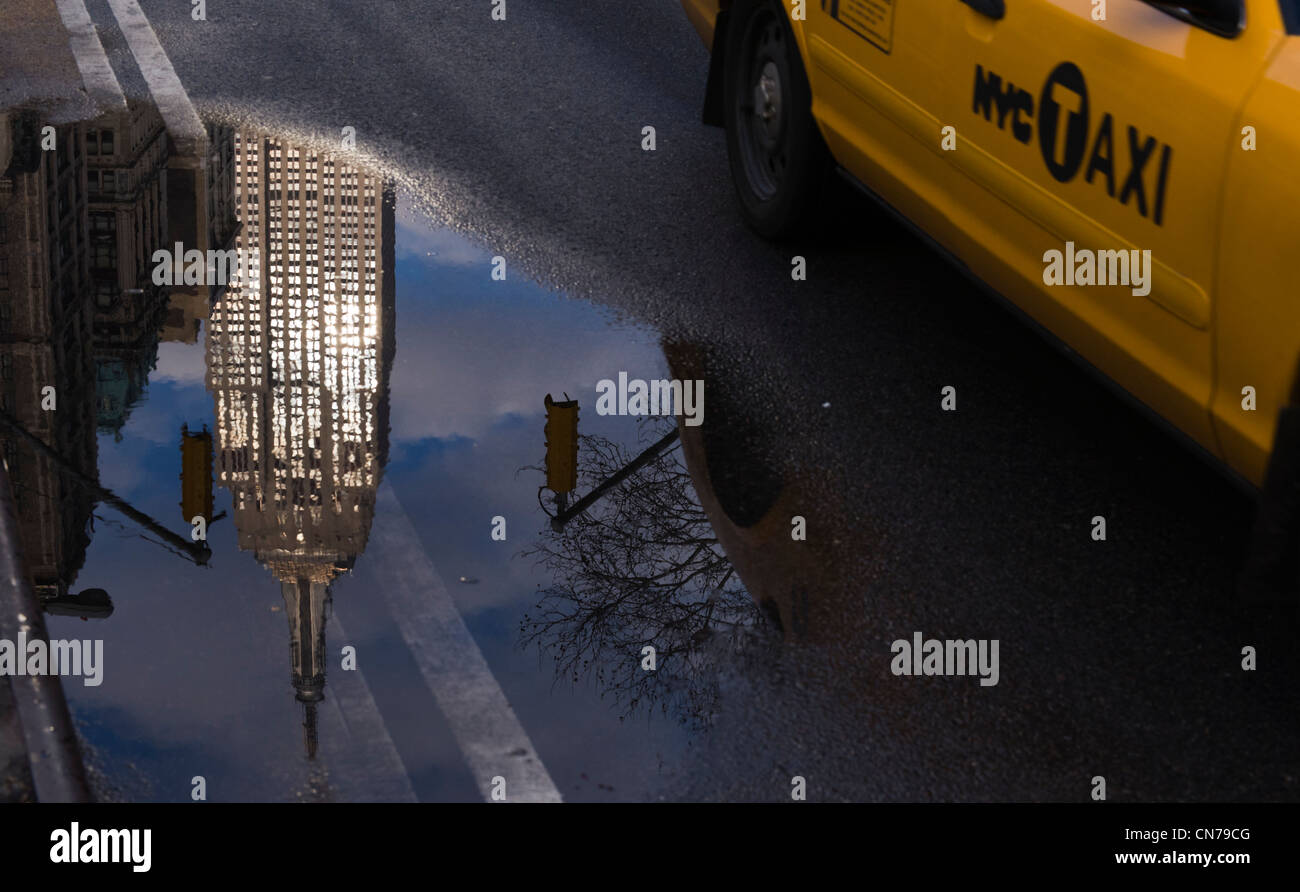 Yellow taxicab drives by a reflection of the Empire State Building 5th Avenue in New York, NY, USA, Jan 1, 2010. - Stock Image