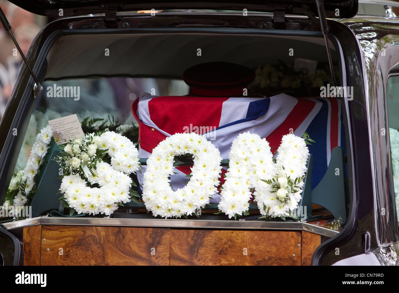A wreath of flowers in the words of 'Son' against the coffin of a dead serviceman covered by the union jack - Stock Image