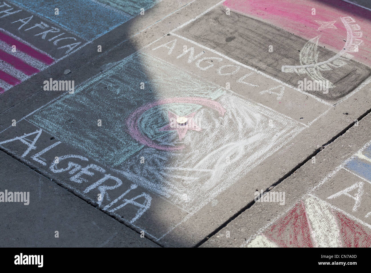 Chalk pavement drawing of flag of Algeria and Angola at the South Bank in London - Stock Image