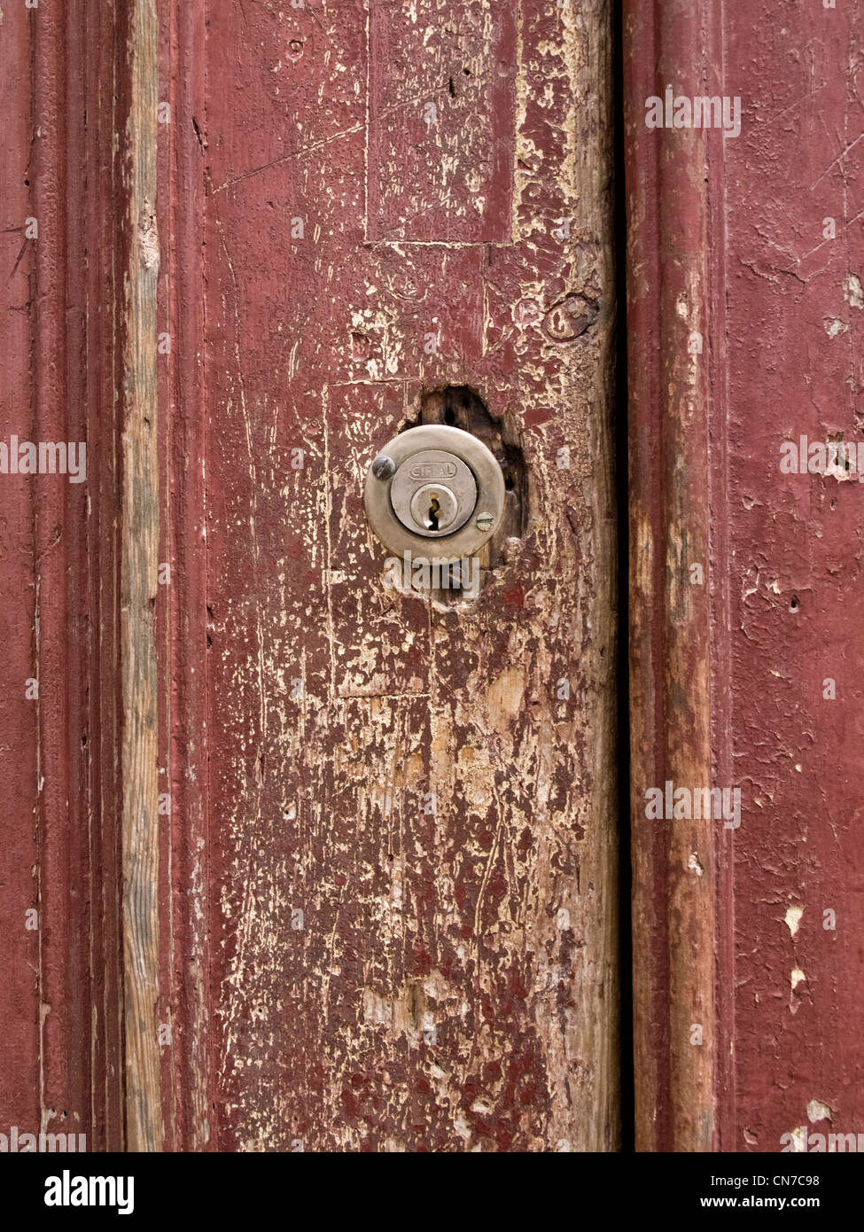 Modern keyhole on an old decaying wooden door - Stock Image