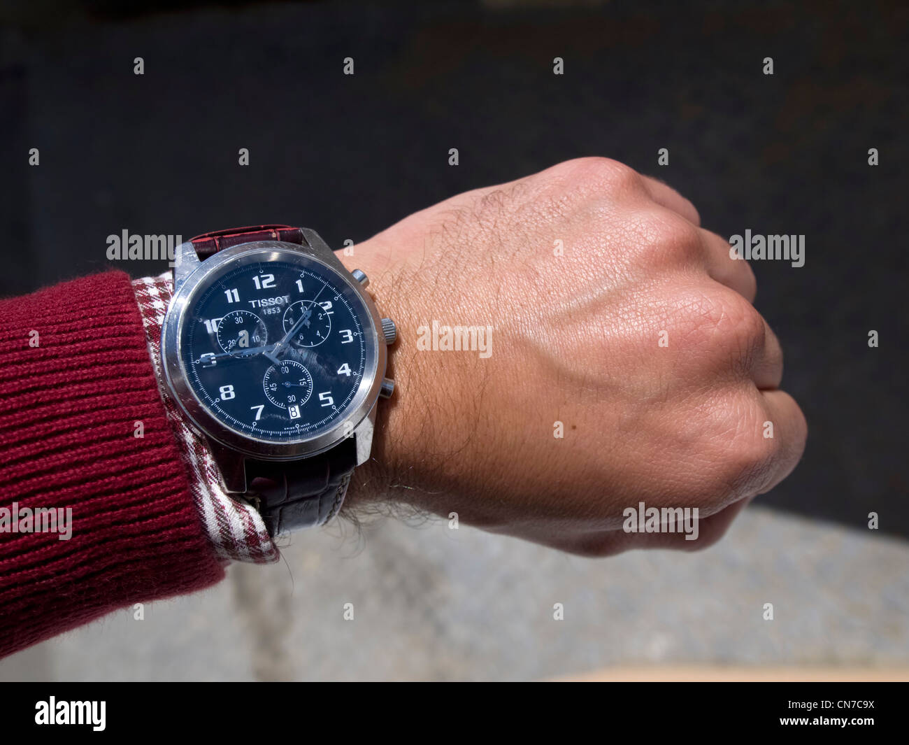 Person using a Tissot wristwatch - Stock Image