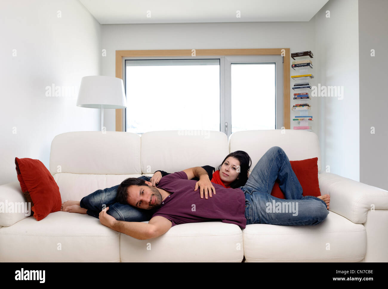 Young couple at home in the living room lying on a white sofa Stock Photo