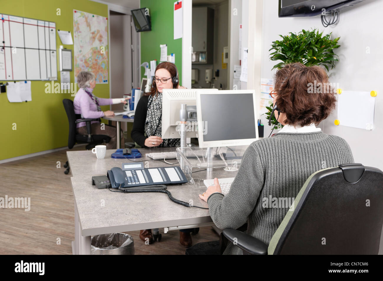 people working in a hospital's call center, answering patients questions over the phone - Stock Image