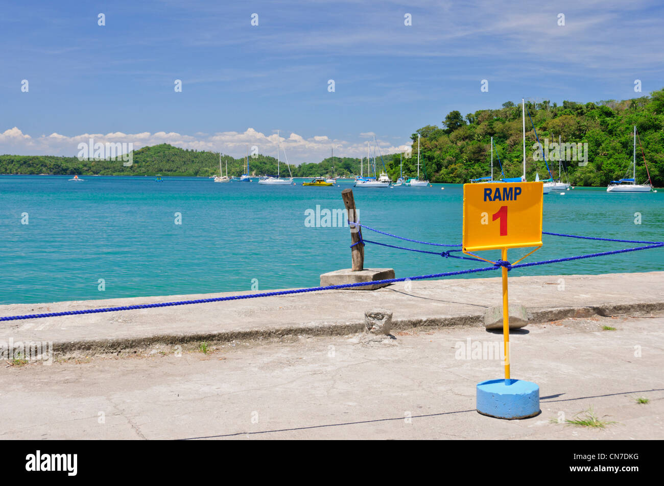 Muelle Pier, Puerto Galera Bay, Oriental Mindoro, Philippines, Southeast Asia, blue ocean water sky, sailing yachts, sign Ramp 1 Stock Photo