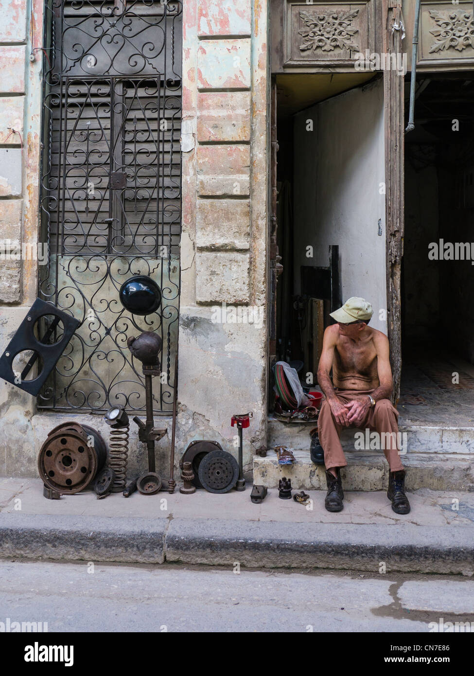 A middle-aged Cuban man sits on the front stoop of his house selling used auto parts in Havana, Cuba. Stock Photo