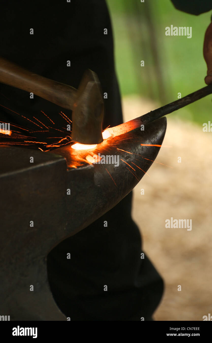 A blacksmith working red hot iron on an anvil. - Stock Image