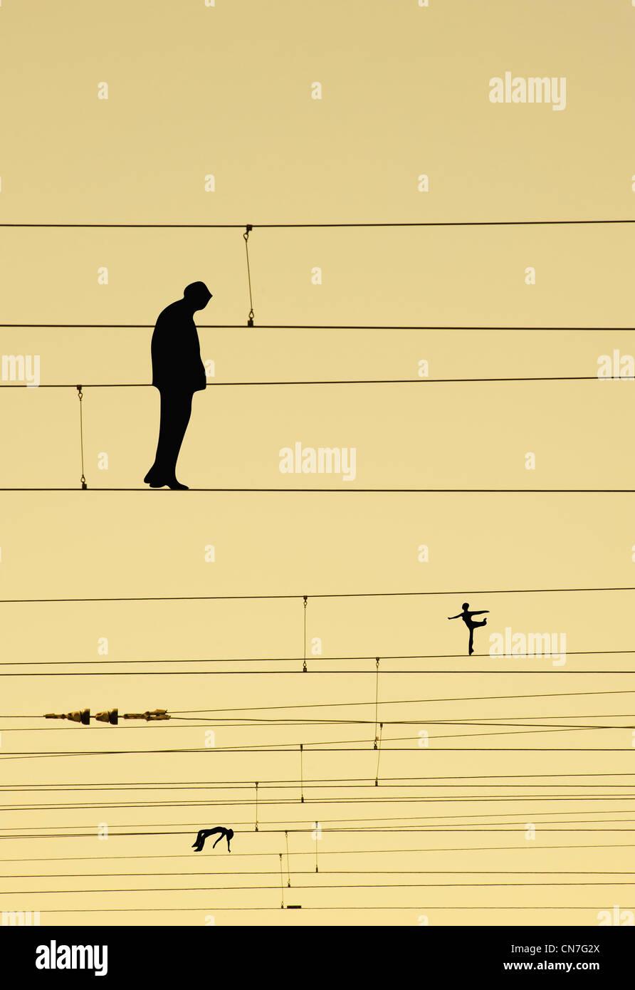 Man walking, balancing on wires. Woman balancing on wires on one leg. Woman lying on the wires. - Stock Image