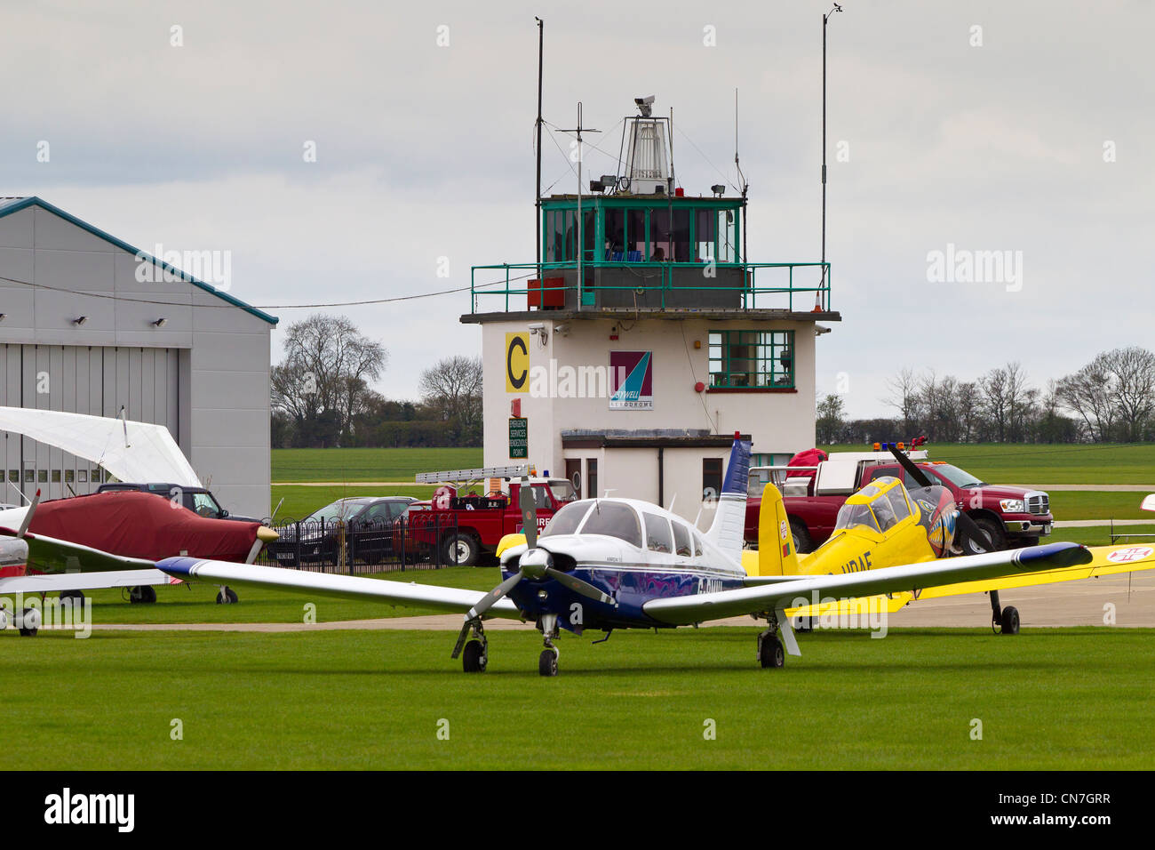 Light aircraft in front of Control Tower Sywell Aerodrome Northamptonshire - Stock Image