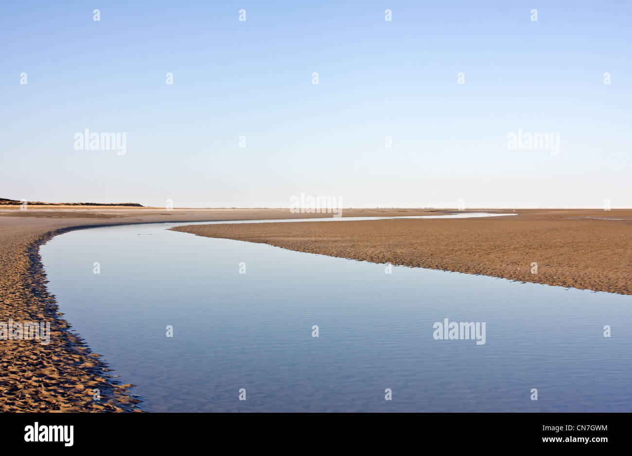 A creek on a deserted beach at ebb tide. - Stock Image