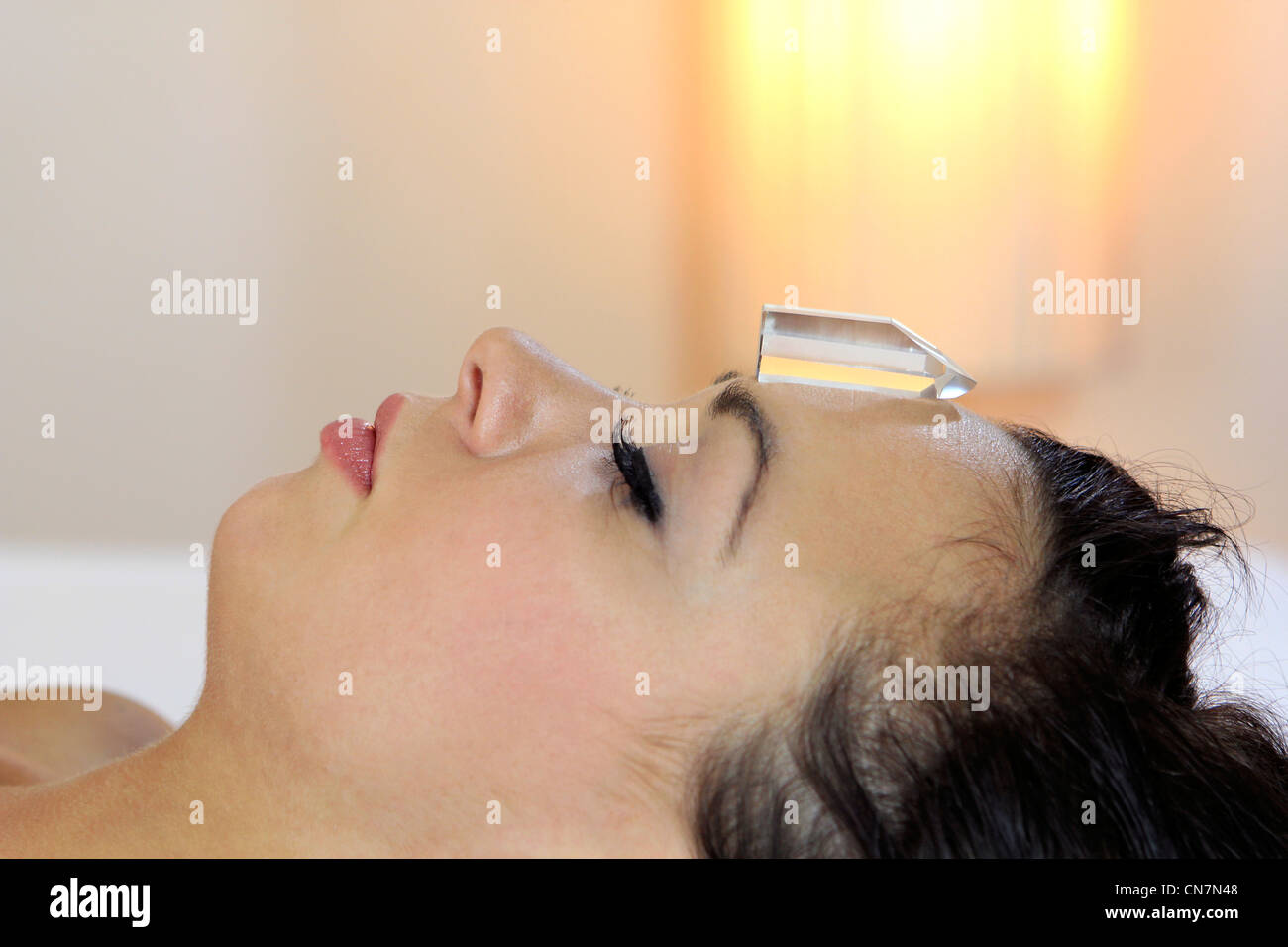 Woman makes a gemstone therapy, alternative healing method - Stock Image