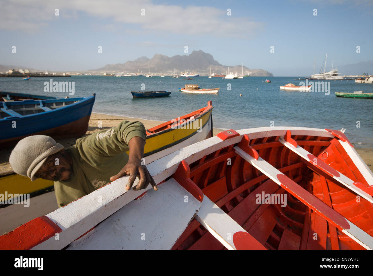 Cape Verde, Sao Vicente island, Mindelo, a fisherman maintains its boat, far off the mountain Montecara Stock Photo