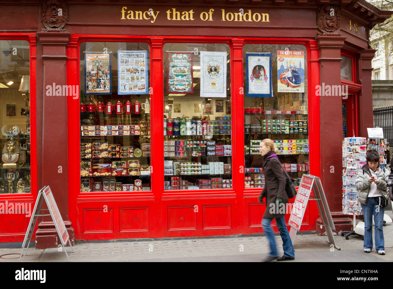 People walking past a shop selling traditional English gifts, London, England, UK - Stock Image