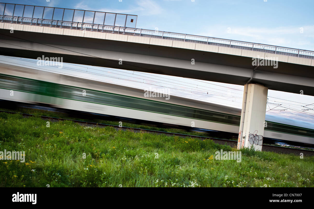 fast train going swiftly through summer landscape and passing under a highway bridge - Stock Image