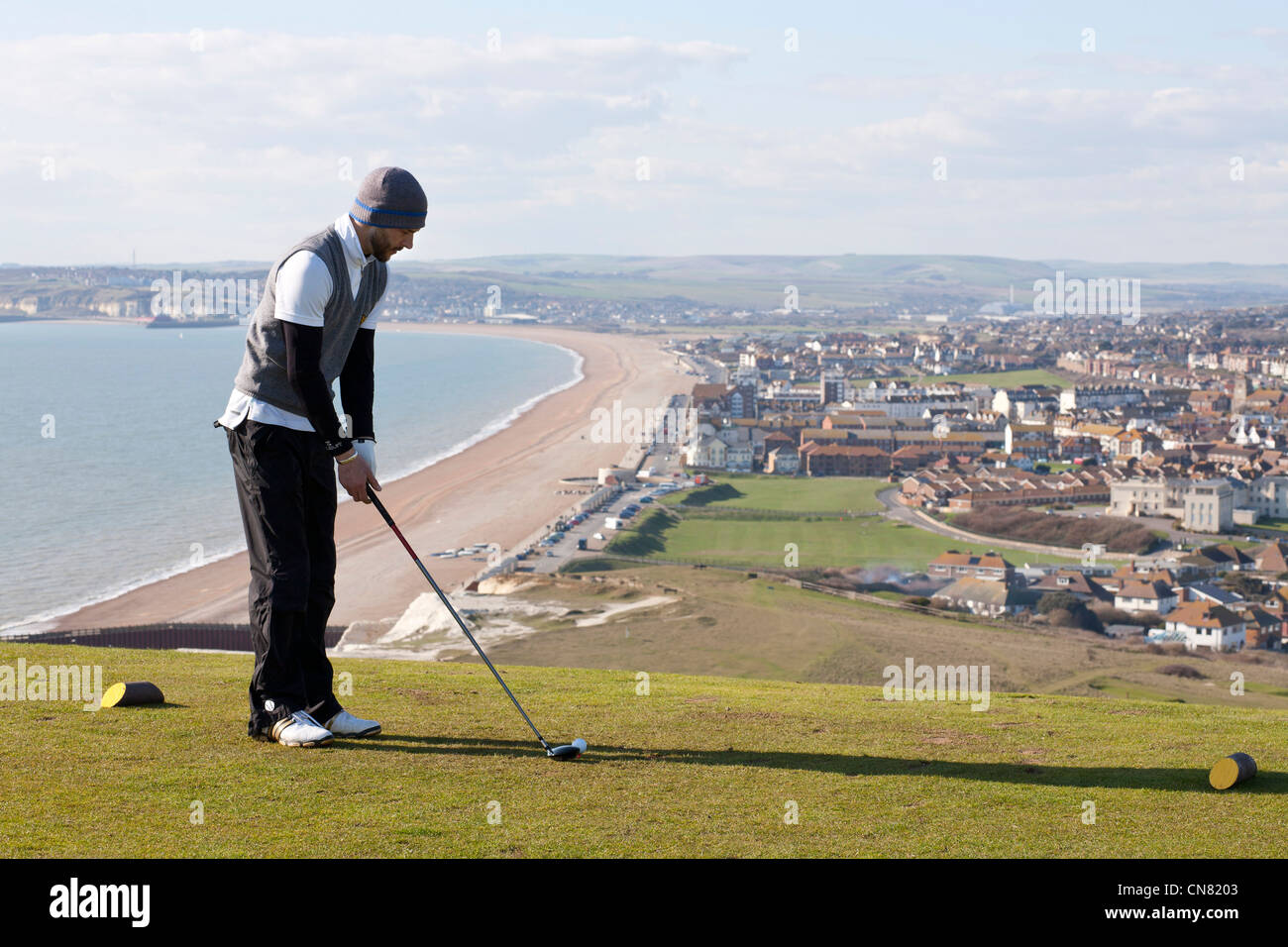 A golfer gets ready to tee off on the 18th hole at Seaford Head golf course East Sussex looking towards Tidemills - Stock Image