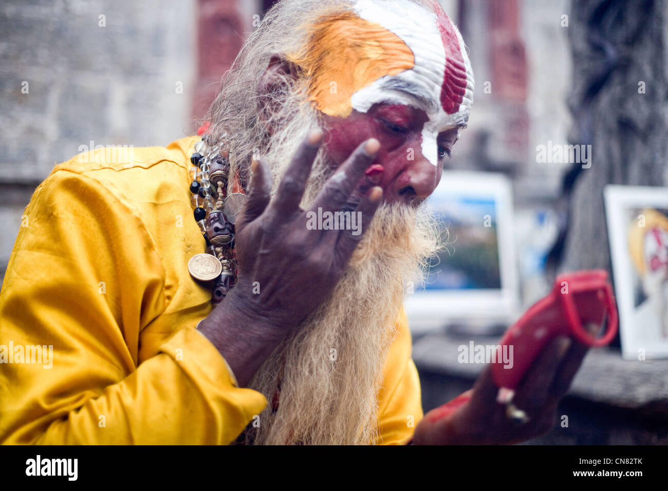Sadhu applying auspicious marks (tilak ) during Shivaratri at Pashupatinath , Kathmandu , Nepal - Stock Image