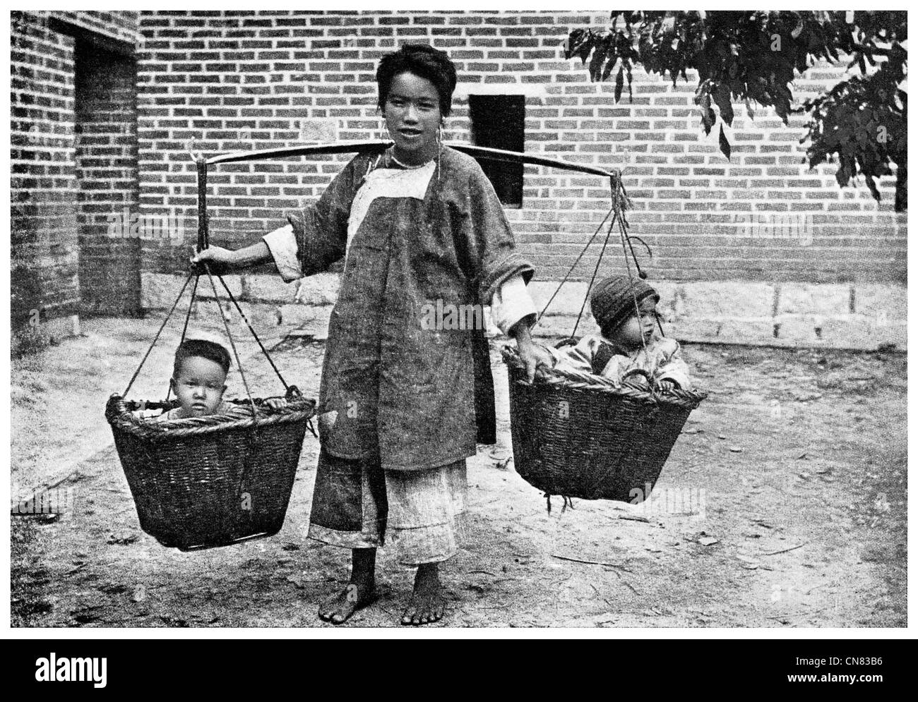 1917 Chinese mother carrying children with a yolk and baskets - Stock Image