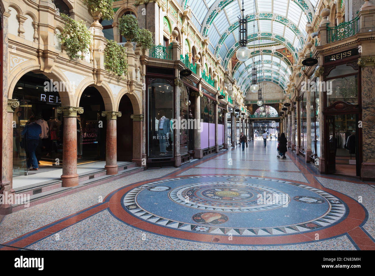 Floor mosaic and traditional upmarket designer shops in County Arcade in Victoria Quarter shopping centre in Leeds - Stock Image
