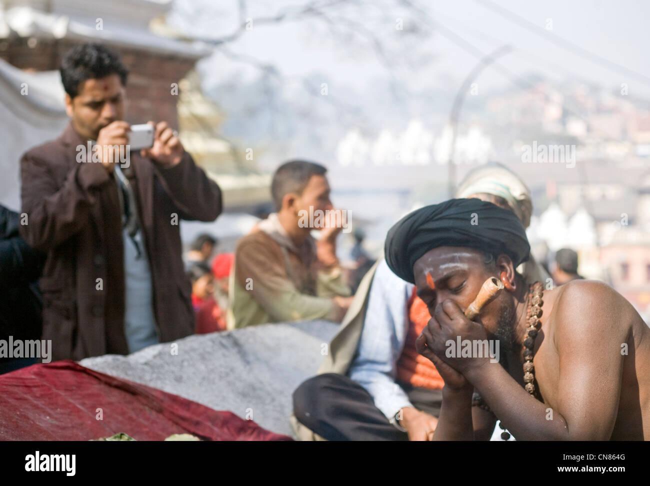 Man photographing sadhu smoking pipe during the annual Shivaratri  festival at  Pashupatinath temple , Kathmandu Stock Photo