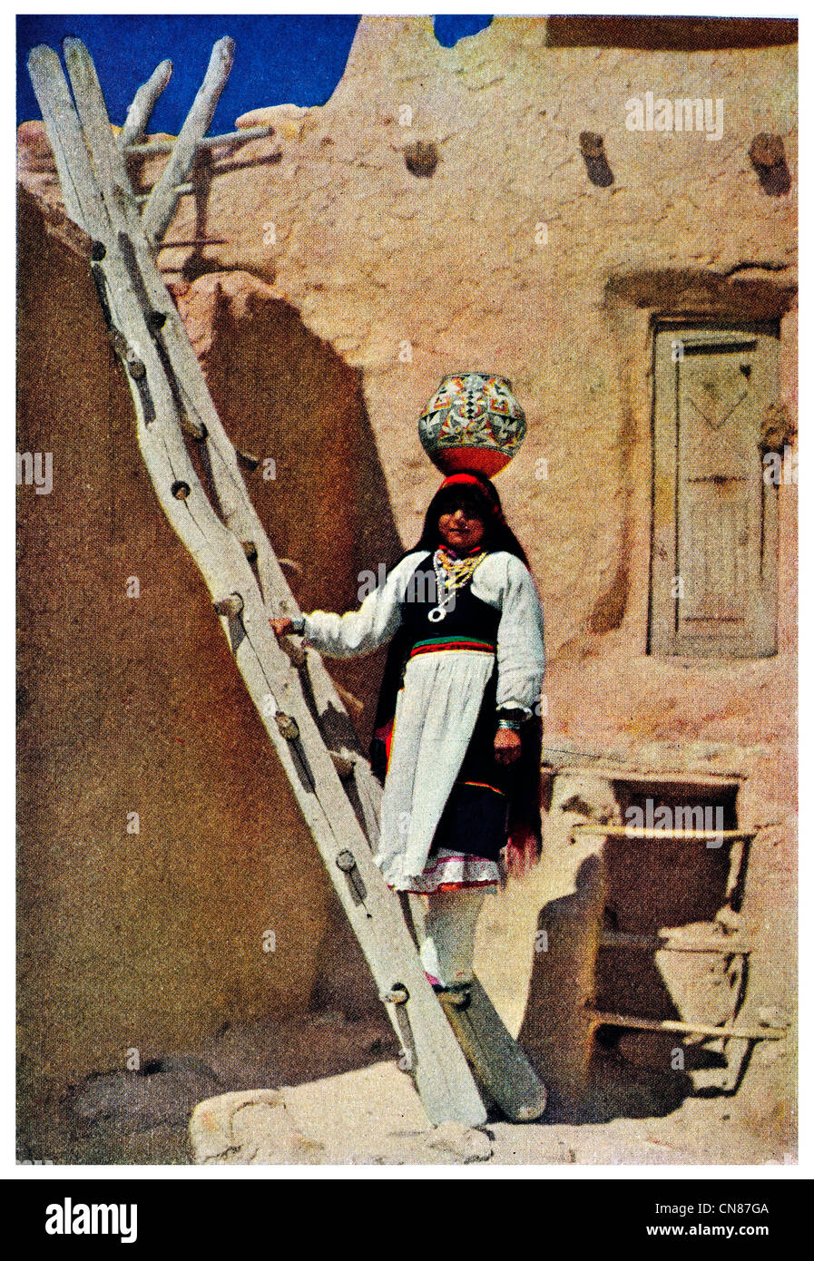 First published 1916 Water carrier of Acoma New Mexico mud brick house ladder wooden wood - Stock Image