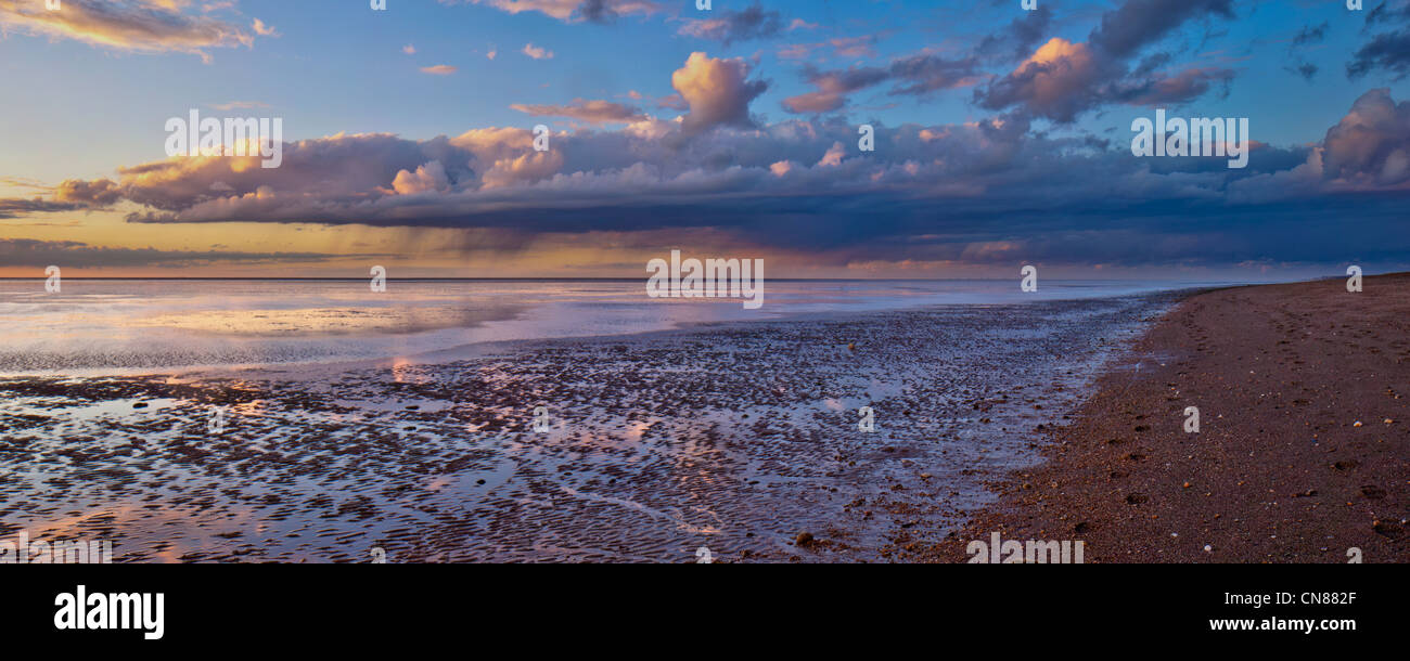 Panorama of autumn sunset and showers on tranquil deserted beach at low tide at Snettisham, Norfolk, UK Stock Photo