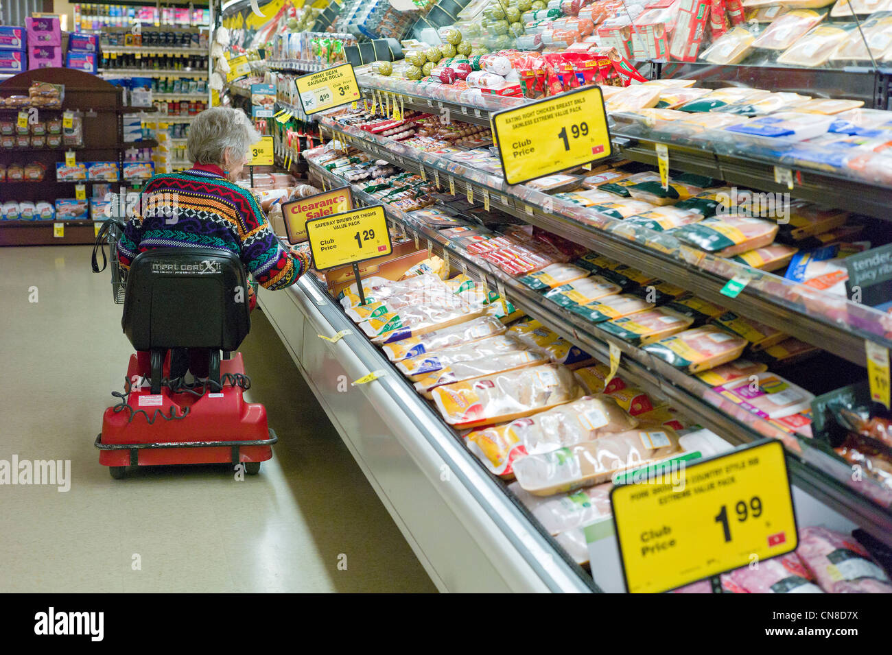 Older woman shopping from her handicap cart at a Safeway grocery store, Salida, Colorado, USA - Stock Image