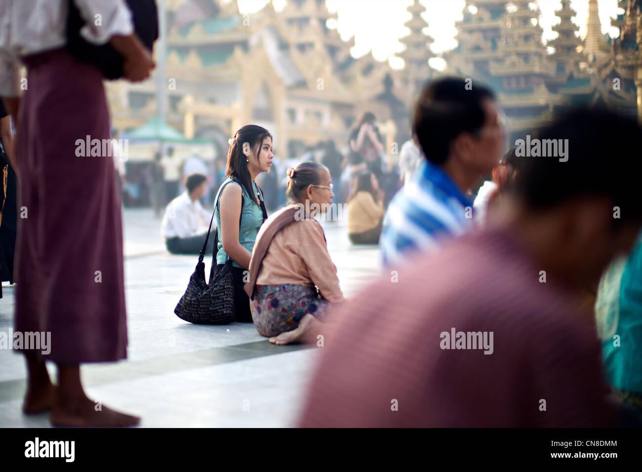 Burmese women pray in at the sacred Buddhist site of Shwedagon Paya, Yangon (Rangoon), Myanmar (Burma) - Stock Image