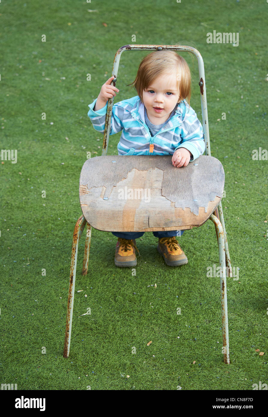 Baby child girl standing with old chair in green grass field - Stock Image