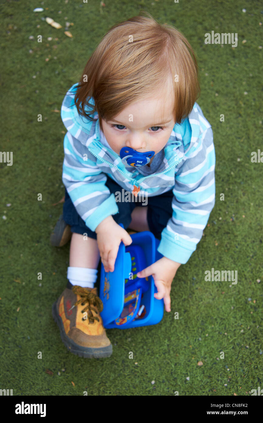 Little child girl with pacifier sitting on the grass and playing with toy phone - Stock Image