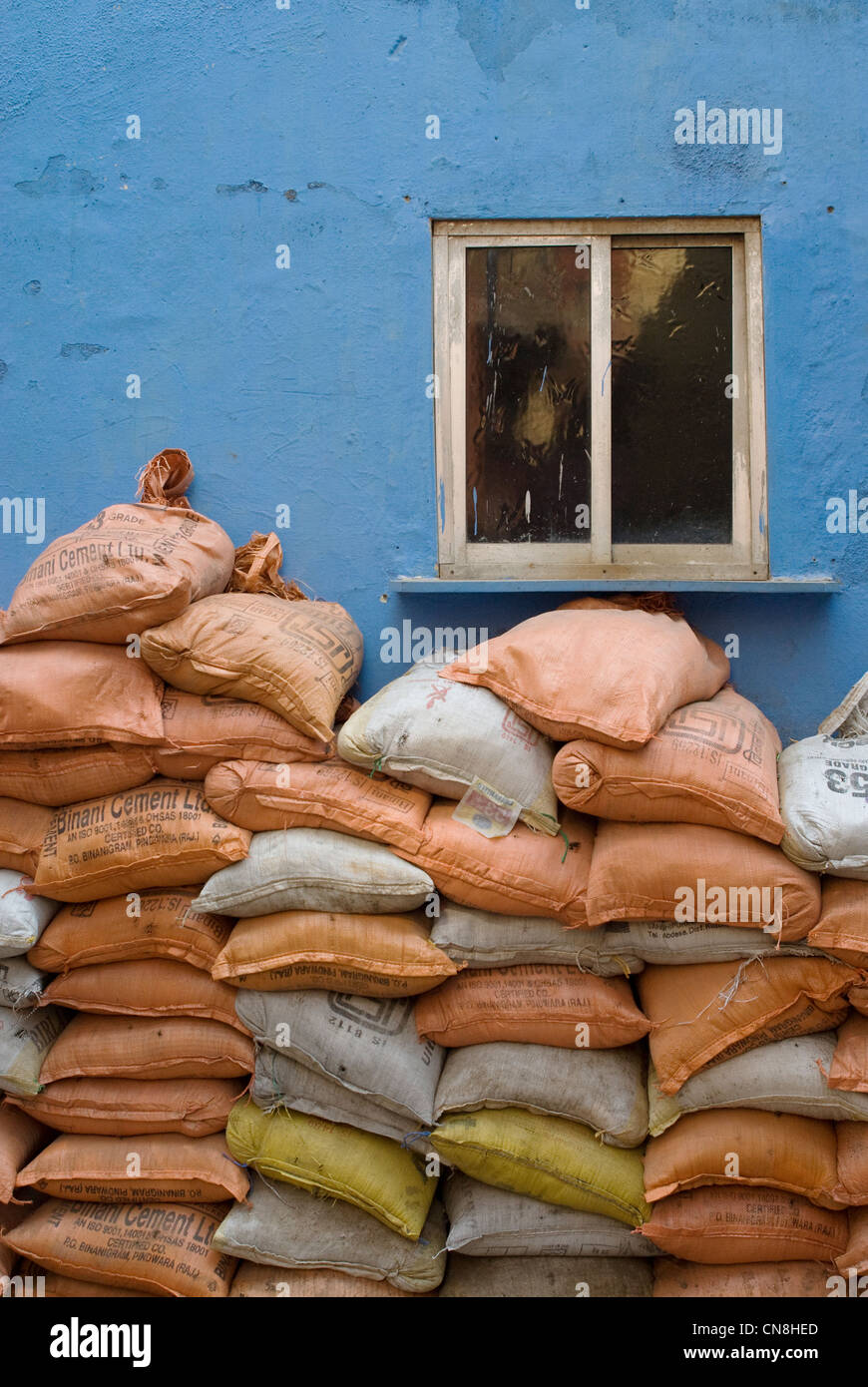 Sacks of sand placed in front of a blue wall with small window - Worli-Kohliwada - Stock Image
