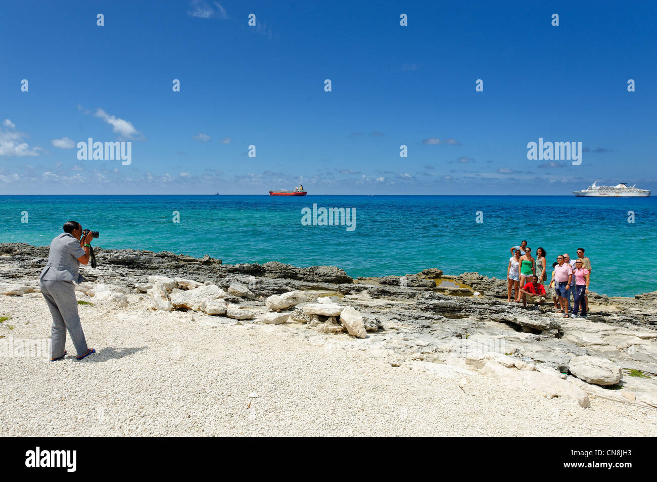 Bahamas, Grand Bahama Island, Eight Mile Rock, tourists taking a picture in front of the ships entering the port - Stock Image