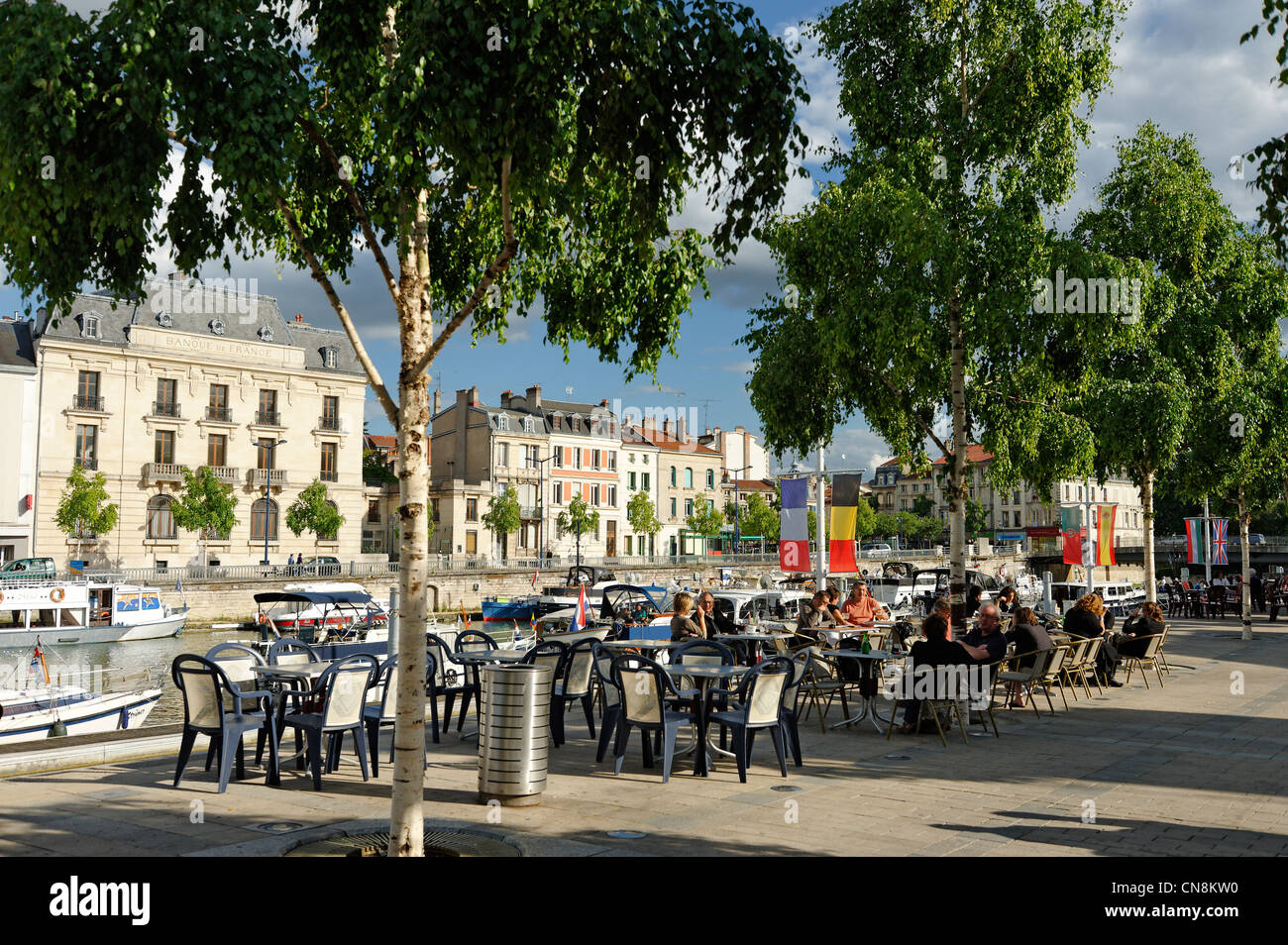 France, Meuse, Verdun, Quai de Londres, sidewalk cafe on a pedestrian walkway along the Meuse river, consumers sitting - Stock Image