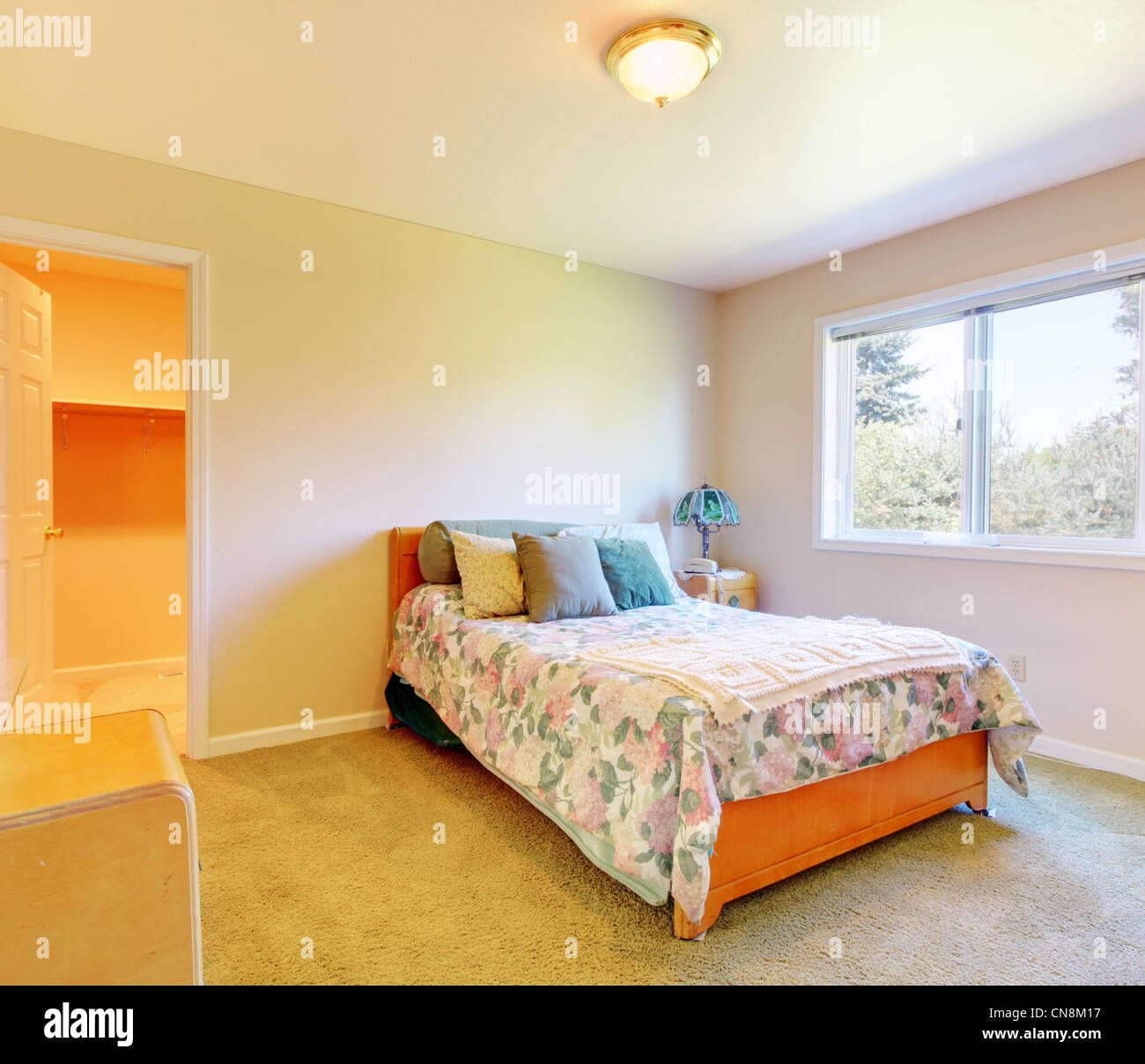 Small Bedroom With Simple Bed And Blue Pillows And Beige Walls Stock Photo Alamy