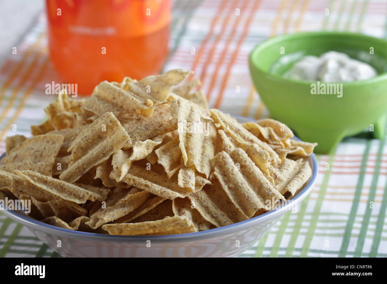 Bowl Of Sun Chips With Herb Dip And Orange Soda All On A Striped