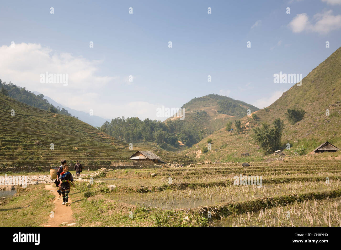 Black Hmong hill tribe girls walking on trail in Lao Chai village near Sapa town, Vietnam Stock Photo