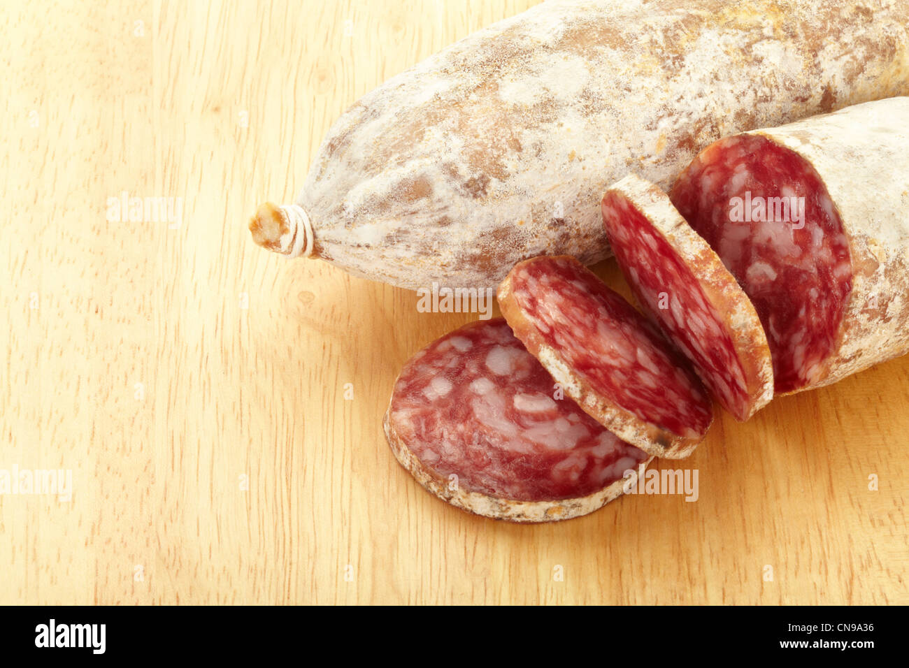 Sliced salami on cutting board - Stock Image