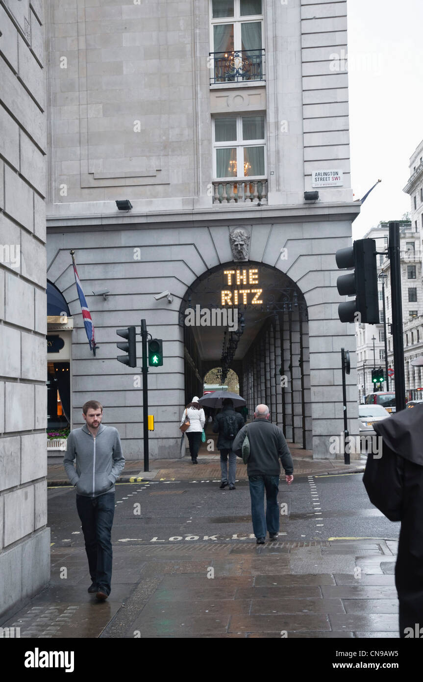 People walking by The Ritz Hotel, Piccadilly, on a dull wet, grey day - an ordinary - yet typical London scene. - Stock Image