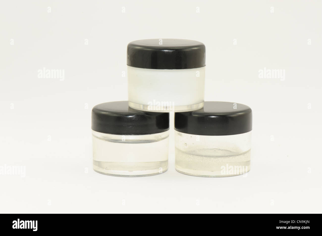jars 3 clear plastic jars with black plastic lids opaque liquid inside taken on a white background - Stock Image