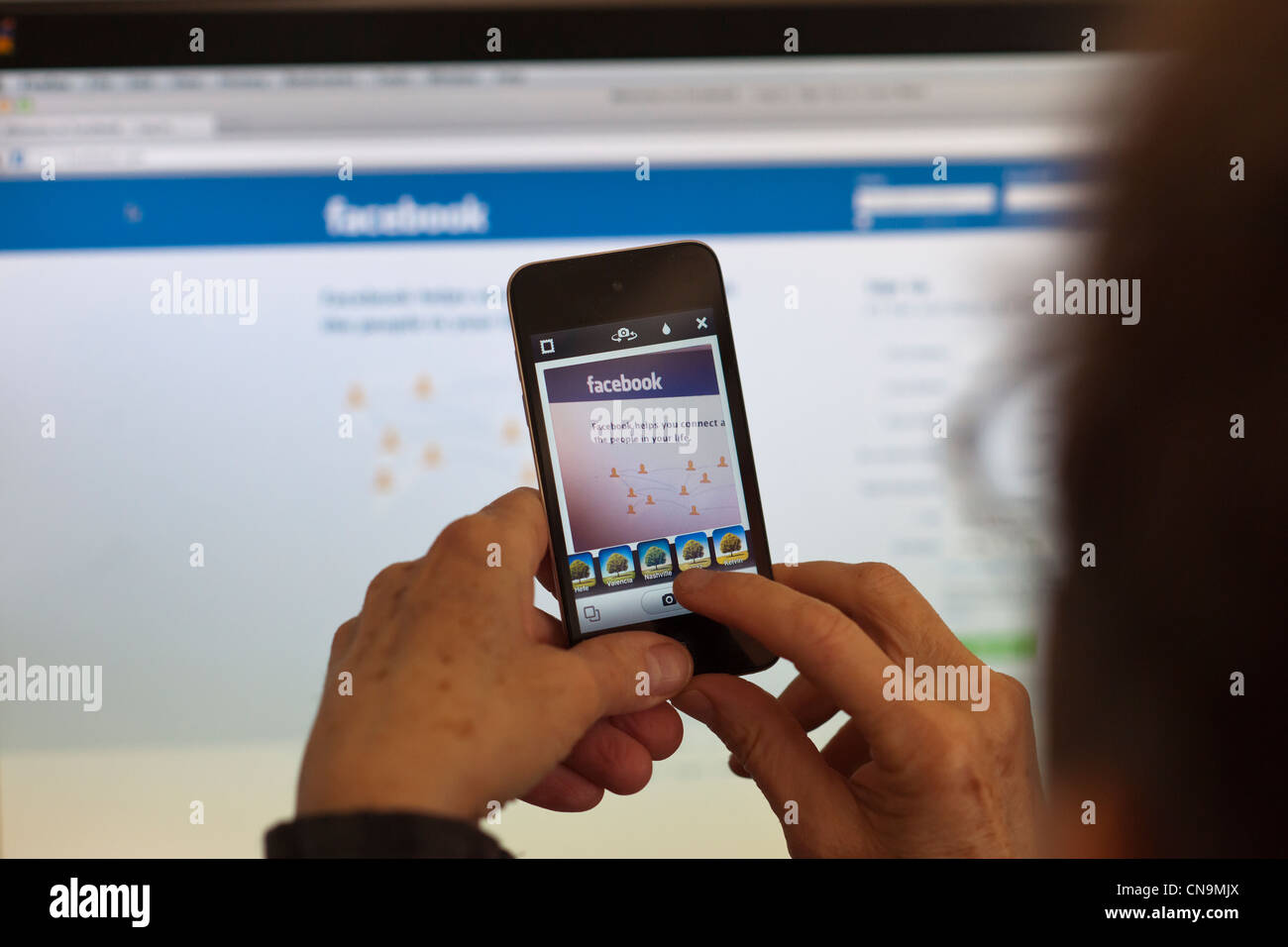 A woman holds her iPod touch and photographs the Facebook web page using an Instagram app - Stock Image