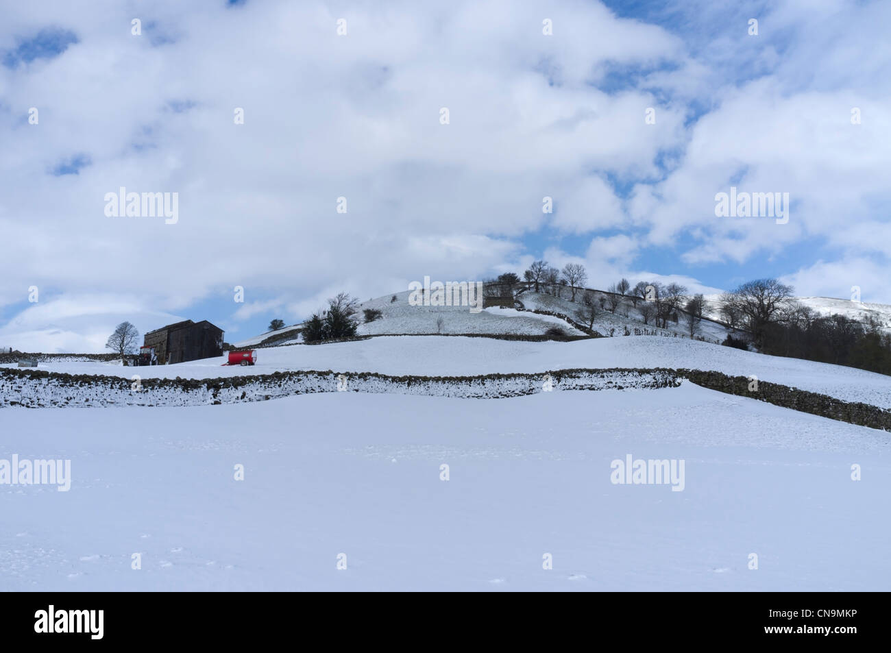A red muck-spreader in a snow covered meadow, Swaledale, Yorkshire, England - Stock Image