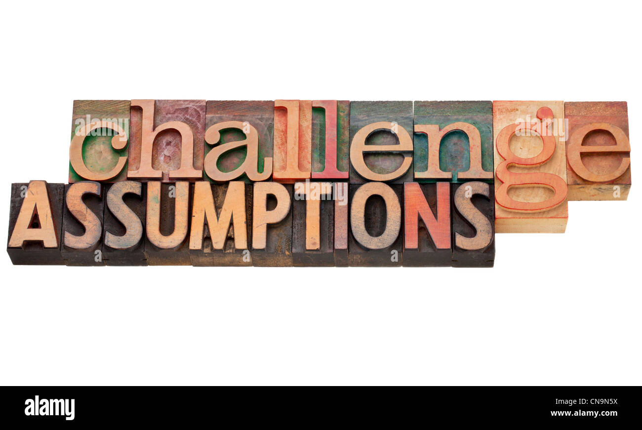 challenge assumptions - isolated text in vintage letterpress wood type - Stock Image