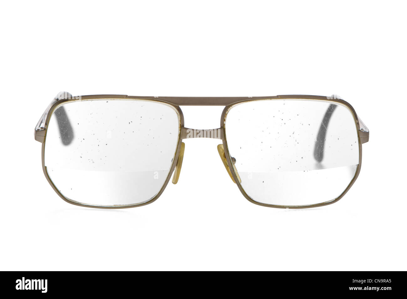 Very old, dirty, beat-up eyeglasses with thick bifocal lens in gold ...