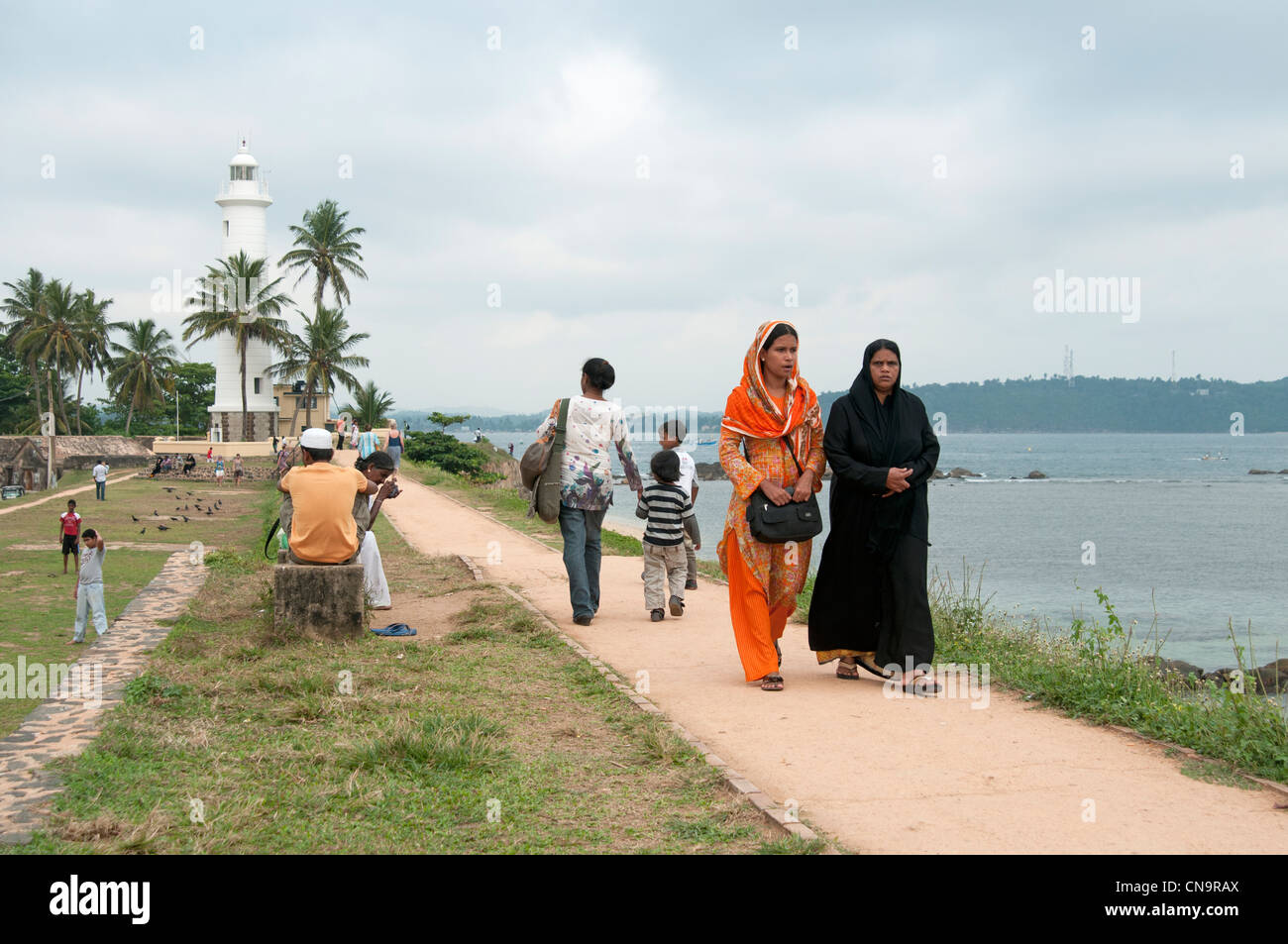 Muslim and Hindu families walking along the ramparts of the Galle Fort Sri Lanka with the lighthouse in the background - Stock Image